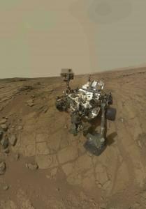 Figure 2: Autoportrait de Curiosity à Yellowknife Bay. Le trou résultant du premier forage (John Klein) est visible sur la roche, à coté du trou d'essai. Cumberland a été foré ultérieurement à 2,75 m de John Klein. Crédit image NASA/JPL-Caltech/MSSS