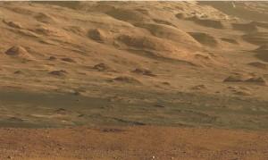 Figure 1 : Terrains à la base du Mont Sharp (Aeolis Mons), actuellement explorés par le robot Curiosity. Les sondes en orbite autour de Mars y ont détecté les signatures spectrales de minéraux hydratés, dont de ceux de la nontronite, un phyllosilicate (ou argile), dans laquelle des molécules organiques pourraient être préservées. (crédits : NASA/JPL/MSSS/Ronald pour UMSF)