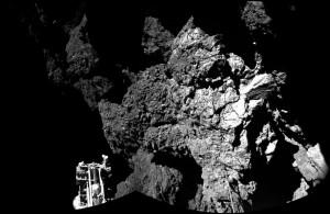 Surface de la comète 67P/Churyumov-Gerasimenko vue par les caméras CIVA de l'atterrisseur Philae. Un des trois pieds de l'atterrisseur est visible sur cette image, au premier plan. Ce sol sombre de comète contient peut être des matériaux de base qui ont permis à la vie d'émerger un jour sur Terre (crédits : ESA/Rosetta/Philae/CIVA)